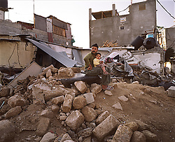 A Palestinian man and his son are seen sitting  on the remains of their home, which was destroyed in an Israeli airstrike, Beit Hanoun, Gaza Strip, Palestinian Territories, Nov. 16, 2006.  According to Human Rights Watch, since September 2005, Israel has fired about 15,000 rounds at Gaza while Palestinian militants have fired around 1,700 back.