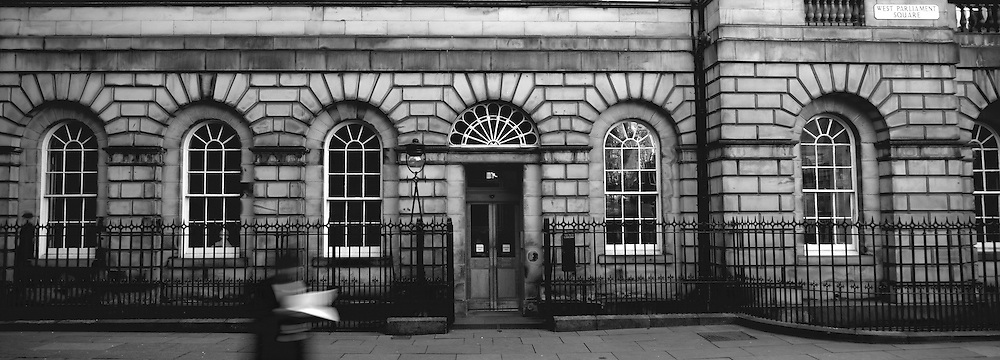 Signet Library with man walking past holding court papers in black and white, Edinburgh