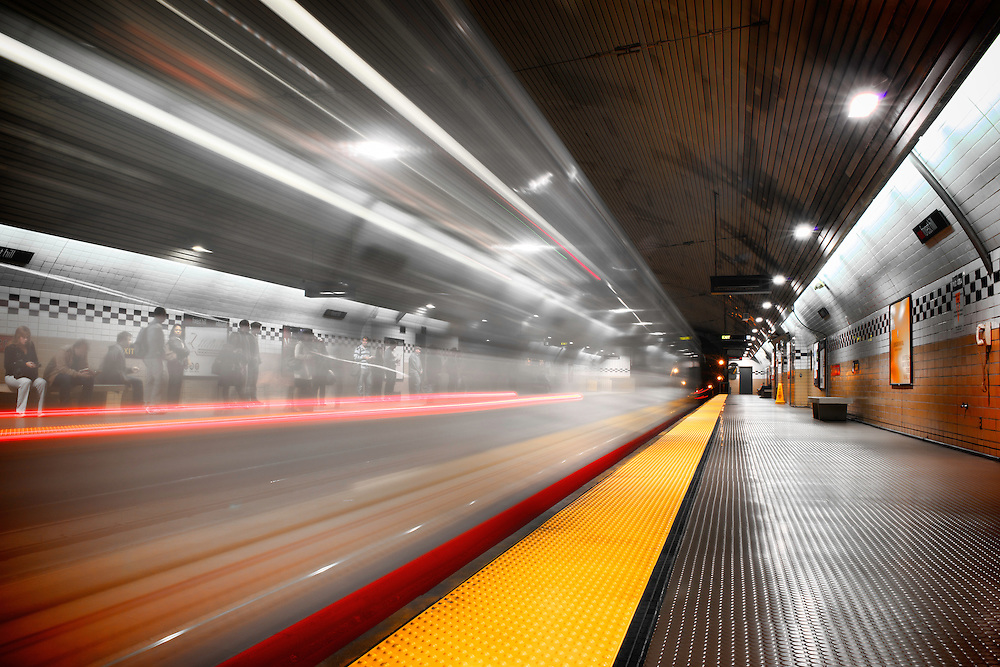 An outbound train passes passengers waiting on the opposite platform for an inbound train at Forest Hill Station | July 18, 2012
