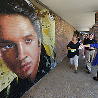 Jan Miller, center of Mississippi Main Street Association reacts as she sees the newest Elvis mural on the wall at Reed's Department Store on West Main Street in Tupelo Tuesday.