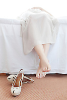 Low section of young woman lying in bed with shoes on floor