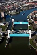 Nederland, Zuid-Holland, Capelle aan den IJssel, 20-03-2009; stormvloedkering in de Hollandsche IJssel. Bij storm en dreigend hoog water wordt een van de twee schuiven naar beneden gelaten, de tweede schuif dient als reserve. De scheepvaart kan de gesloten kering paseren via de naastgelegen schutsluis. De stormvloedkering maakt deel uit van de Deltawerken en is als eerste voltooid in 1958. Ten tijde van De Ramp - watersnood 1953 - werd het zeewater door de storm opgestuwd en dreigde de verzwakte rivierdijken in het achterland het te begeven waardoor grote van het laag gelegen westen van Nederland ondergelopen zouden zijn..Netherlands, Capelle at the river IJssel, near Rotterdam: storm surge barrier, protects the highly populated western part of Holland, which lies below sea level. In case of storm and threat of high water, one of the two doors is lowered into the river (the second door is a spare one). The lock next to the barrier allows shipping when the barrier is closed.Swart collectie, luchtfoto (toeslag); Swart Collection, aerial photo (additional fee required).foto Siebe Swart / photo Siebe Swart