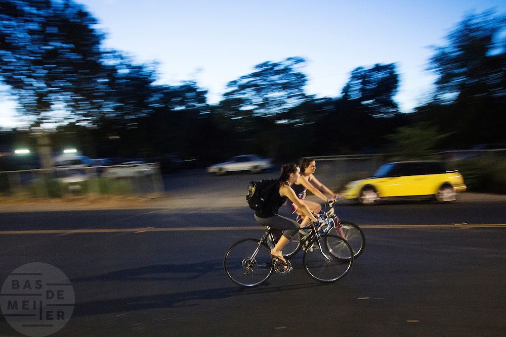 In de Amerikaanse plaats  Davis, California rijden fietsers 's avonds over straat.<br /> <br /> In the American town Davis, California cyclists ride in the evening.