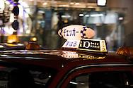 Tokyo Taxi parked in Harajuku district picks up during late night bar crawl. Tokyo, Japan.
