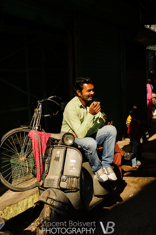 a man drinking tea (chai) sitting on his motorbike in Jodhpur market, India