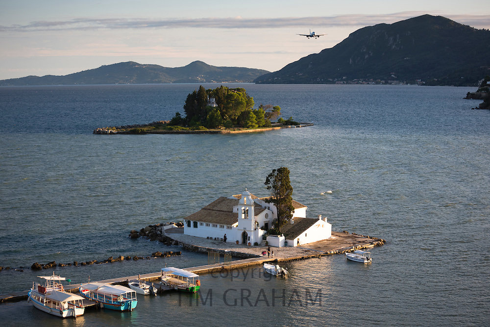Airplane flying over famous monastery Panagia Vlahernon off Kanoni Peninsula in Kerkyra, Corfu Town, Ionian Islands, Greece