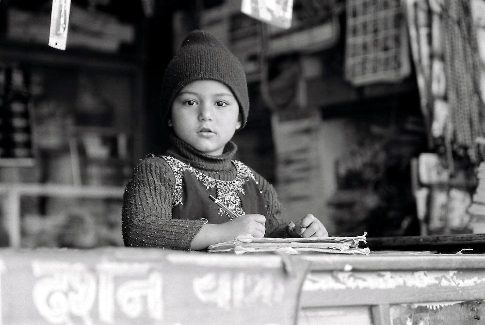 Pour ce jeune népalais qui sort de l'école, c'est l'heure de faire ses devoirs sur le comptoir de la boutique de papa. Kathmandu, Népal. 2008