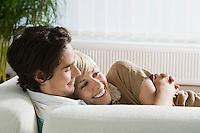 Young couple relaxing on sofa smiling