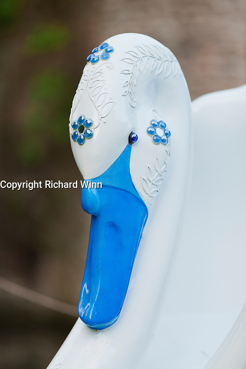 Closeup of the head of a swan decorated with glass crystals; one if the painted swans in Wealls, next to the moat.