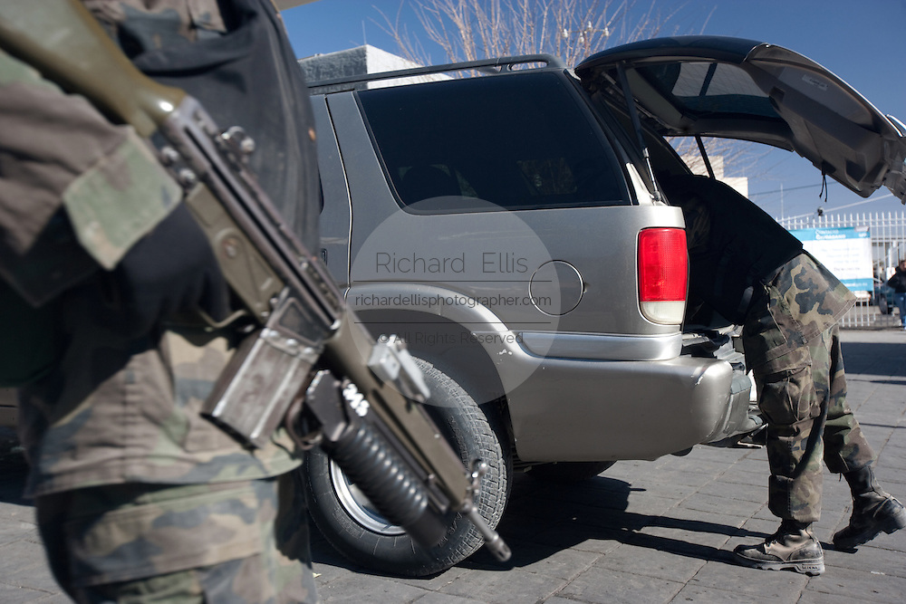 Soldier search a vehicle at the Juarez Avenue border crossing into the USA in Juarez, Mexico January 14, 2009. An ongoing drug war has already claimed more than 40 people since the start of the year. More than 1600 people were killed in Juarez in 2008, making Juarez the most violent city in Mexico.    (Photo by Richard Ellis)