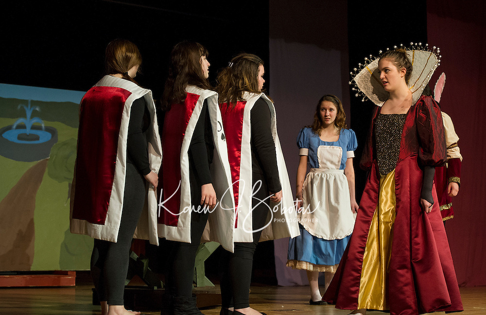 Playing Cards (Cassie Nichols, Allyson McGuire and Ashlyn Morse), Red Queen (Marissa Leyland) and Alice (Olivia Martinson) during Wednesday's dress rehearsal for Winnisquam Regional High School's production of Alice in Wonderland.   (Karen Bobotas/for the Laconia Daily Sun)