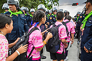 23 NOVEMBER 2012 - BANGKOK, THAILAND:  Thai school children walk home between columns in Thai riot police in Bangkok. Thai authorities have imposed the Internal Security Act (ISA), that enables police to call on the army if needed to keep order, and placed thousands of riot police in the streets around Government House in anticipation of a large anti-government protest Saturday. The group sponsoring the protest, Pitak Siam, said up to 500,000 people could turn out to protest against the government. They are protesting against corruption in the current government and the government's unwillingness to arrest or pursue fugitive former Prime Minister Thaksin Shinawatra, deposed in 2006 coup and later convicted on corruption charges. The current Thai Prime Minister is Yingluck Shinawatra, Thaksin's sister.      PHOTO BY JACK KURTZ