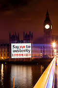 Campaigners and supporters of the Anti Austerity demonstration against government cuts on the 20th of October 2012 project a poster in support of the protest onto the House of Parliament, Westminster. The march against the governments crippling cuts is expected to be the biggest of 2012.