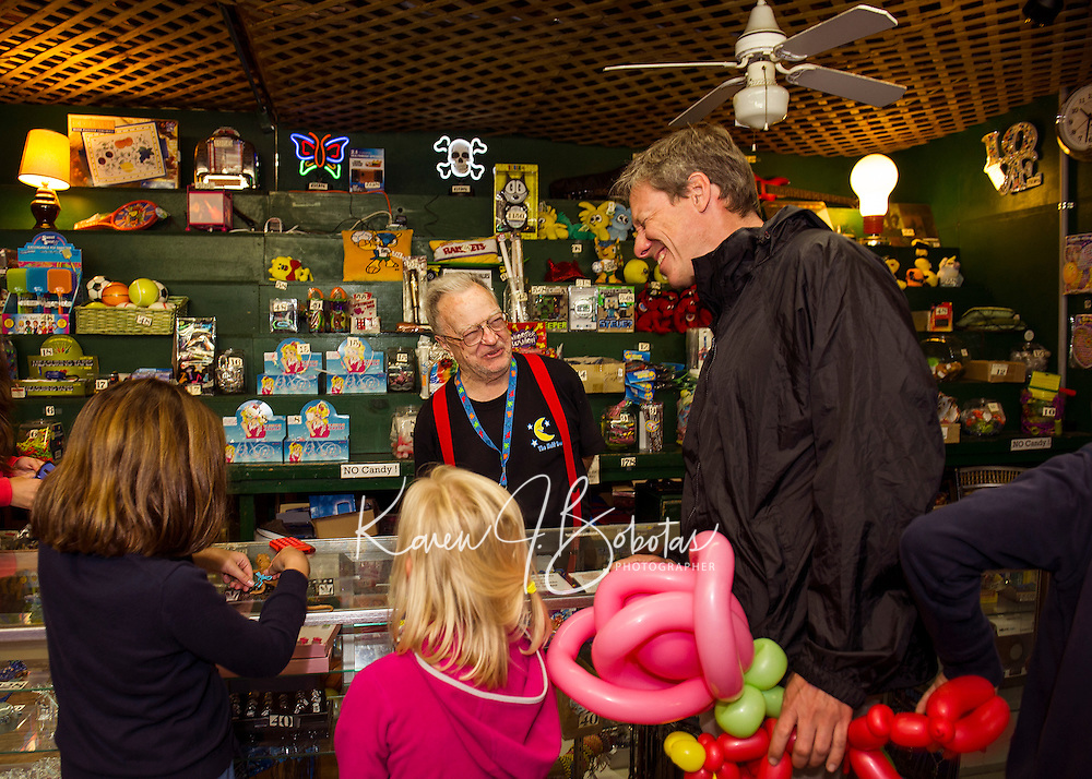 Charlie Walsh of the Half Moon Arcade helps Julia Healey, Suzanne Healey-Parera and Mark Healey at the prize counter on Wednesday afternoon.  (Karen Bobotas/for the Laconia Daily Sun)