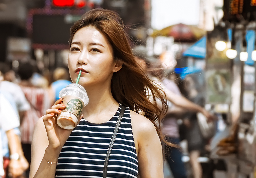 Pretty Asian girl taking a sip of coffee walking on street. NYC 2017