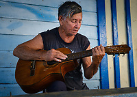 BARACOA, CUBA - CIRCA JANUARY 2020: Cuban male playing guitar in Bahia de Mata, a hamlet close to Baracoa in Cuba.