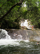 People enjoy sliding at Josephine Falls, within the Wooroonooran National Park, near Babinda, QLD, Australia.