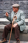 Italy, Sicily, Portrait of a local mature man sits in the village square