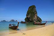 Longtail boats anchored along Phra Nang Beach and Koh Rang Nok island in Krabi, Thailand.