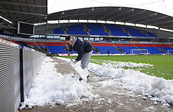 BOLTON, ENGLAND - Saturday, January 26, 2013: Ground staff clear snow from the electronic advertising boards surround the pitch at Bolton Wanderers' Reebok Stadium ahead of the FA Cup 4th Round match against Everton. (Pic by David Rawcliffe/Propaganda)