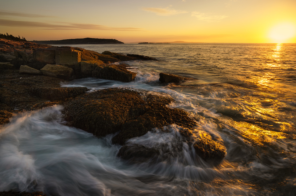 Sunrise breaks on the rocky coast of Acadia National Park, Maine, USA