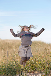 girl jumping in the air in the dunes of East Hampton, NY