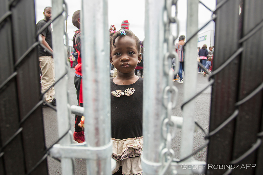 A little girl who crossed the Canada/US border illegally with her family, claiming refugee status in Canada, looks through a fence at a temporary detention centre in Blackpool, Quebec, August 5, 2017.