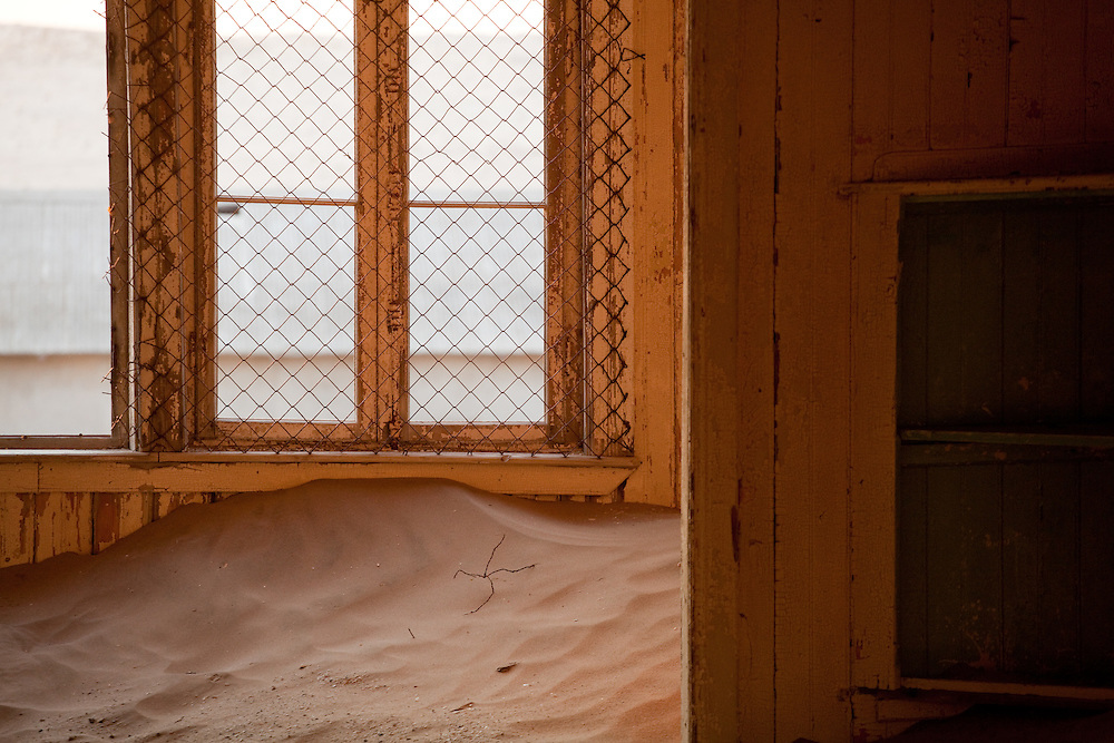 Sand, windows, and shelves, juxtaposed in solitude in Kolmanskop, Namibia