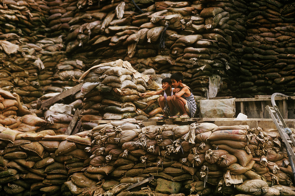 Children sit on sacks of gold ore waste at a ball mill. The waste still contains about 60 percent of unrecovered gold after local processing with mercury. Mount Diwata, Mindanao, The Philippines