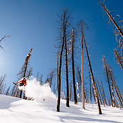 Jim Ryan grabs and air amongst the wildfire burned trees in the Teton backcountry.