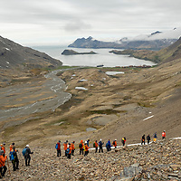 People descend from the Shackleton Hike towards the historic whaling station at Stromness. The Shackleton Hike leads from Fortuna Bay to Stromness on South Georgia Island.
