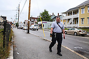 Manchester EMS officer/firefighter paramedic Chris Hickey looks for discarded needles alone a fence in a Manchester, NH, neighborhood Wednesday, Aug. 10, 2016. <br /> To help combat Manchester New Hampshire's huge drug problem, anyone can walk into the main fire station seeking help, they'll get connected with a drug counselor and services. Something like 230 people have shown up in the first couple months and it's quickly spawning copy-cat programs.  <br />    (Cheryl Senter for The Wall Street Journal)