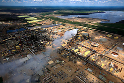 CANADA ALBERTA FORT MCMURRAY 20JUL09 - Aerial view of Syncrude upgrader in the Boreal forest north of Fort McMurray, northern Alberta, Canada...The tar sand deposits lie under 141,000 square kilometres of sparsely populated boreal forest and muskeg and contain about 1.7 trillion barrels of bitumen in-place, comparable in magnitude to the world's total proven reserves of conventional petroleum. Current projections state that production will  grow from 1.2 million barrels per day (190,000 m³/d) in 2008 to 3.3 million barrels per day (520,000 m³/d) in 2020 which would place Canada among the four or five largest oil-producing countries in the world...The industry has brought wealth and an economic boom to the region but also created an environmental disaster downstream from the Athabasca river, polluting the lakes where water and fish are contaminated. The native Indian tribes of the Mikisew, Cree, Dene and other smaller First Nations are seeing their natural habitat destroyed and are largely powerless to stop or slow down the rapid expansion of the oil sands development, Canada's number one economic driver...jre/Photo by Jiri Rezac / GREENPEACE..© Jiri Rezac 2009