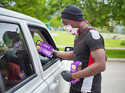 21 MAY 2020 - DES MOINES, IOWA: NADIR SHIBAZ, a volunteer at an emergency food distribution in Evelyn K. Davis Park in central Des Moines, hands a box of Girl Scout cookies to people in a car. All of the 485 meals were distributed in about an hour. The economic fallout of the pandemic is being felt throughout Iowa. On May 21, 2020, Iowa reported that 187,375 people had filed for unemployment since the beginning of the COVID-19 pandemic and resulting economic shutdown. Emergency food pantry has also increased in that time, as many Iowans in low wage jobs used emergency food banks and pantries for the first time. The Food Bank of Iowa said Thursday that demand in April 2020 was 31% higher than demand in April 2019, mostly because of unemployment caused by the Coronavirus (SARS-CoV-2) pandemic. The emergency food distribution Thursday was organized by the city of Des Moines, Food Bank of Iowa, Central Iowa Shelter and Services, Urban Dreams and Orchestrate Hospitality.      PHOTO BY JACK KURTZ
