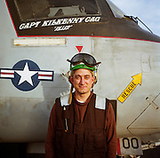 A US Navy electrician looks straight into the camera wearing a brown colour-coded uniform and beneath the cockpit of an EA-6B Prowler, a communications and intelligence-gathering patrol aircraft on the deck of the aircraft carrier USS Harry S Truman, on patrol off Kuwait in the Persian Gulf enforcing the coalition's no-fly zone over Iraq. Behind him are the signs and emblems of the US Navy aircraft that is parked on the deck of this carrier so named after the US President who was in office from 1945 to 1953. Picture from the 'Plane Pictures' project, a celebration of aviation aesthetics and flying culture, 100 years after the Wright brothers first 12 seconds/120 feet powered flight at Kitty Hawk,1903. .