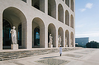 """ROME, ITALY - 15 OCTOBER 2018: An artisan working for FENDI walks by the statues at the Fendi Headquarters at the Palazzo della Civiltà Italiana, also called the """"Colosseo Quadrato"""" (Square Colosseum), in Rome, Italy, on October 15th 2018.<br /> <br /> The LVMH Journées Particulières is is a series of exhibitions that show the creations and history of the LVMH fashion houses. The driving theme behind the Journées Particulières is to allow the general public to discover the inner workings of the Houses which are part of the LVMH heritage.The LVMH Journées Particulières exhibition by fashion house FENDI takes place at their headquarters at the Palazzo della Civiltà Italiana, also called the """"Colosseo Quadrato"""" (Square Colosseum),  an outstanding jewel of the 20th century Roman architecture."""