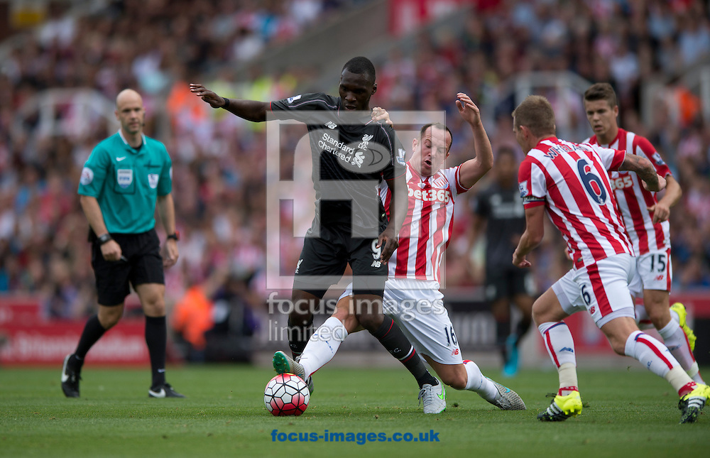 Christian Benteke of Liverpool (centre) is closed down by Charlie Adam of Stoke City during the Barclays Premier League match at the Britannia Stadium, Stoke-on-Trent<br /> Picture by Russell Hart/Focus Images Ltd 07791 688 420<br /> 09/08/2015