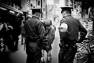 Police question a homeless man in Shinjuku possibly thinking he had shoplifted goods from one of the many electronics shops in this particular neighborhood, Tokyo, Japan.