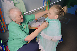 Play Worker helping young girl to put on fancy dress outfit,