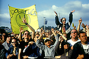 Crowd cheering, someone holding up a banner reading 'Cool As Fuck', Glastonbury Festival, UK, 2000's