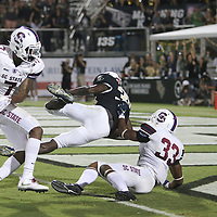 ORLANDO, FL - SEPTEMBER 08:  Greg McCrae #30 of the UCF Knights leaps into the end zone for a touchdown past Zafir Kelly #7 and Chris Adams #33 of the South Carolina State Bulldogs during a football game at Spectrum Stadium on September 8, 2018 in Orlando, Florida. (Photo by Alex Menendez/Getty Images) *** Local Caption *** Greg McCrae; Zafir Kelly; Chris Adams