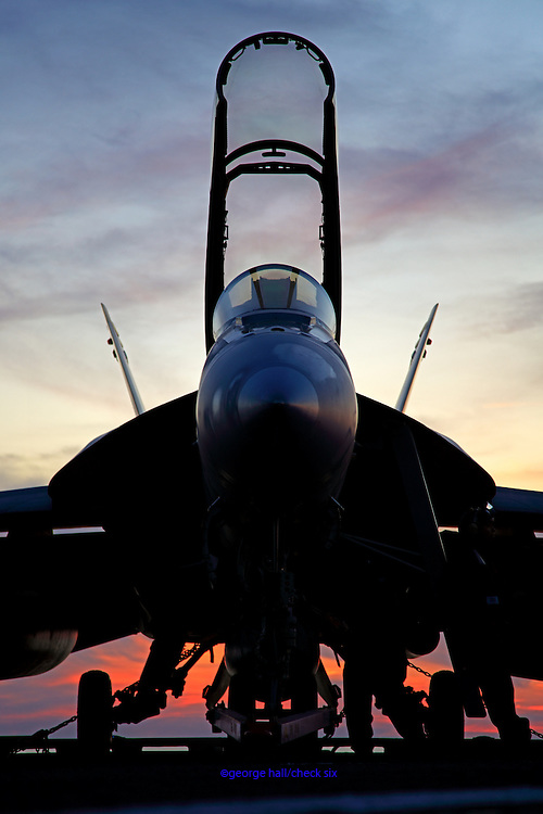 A Boeing F/A-18F Super Hornet, AC 100 166661 from VFA-32 'Swordsmen' rests on the deck of CVN-75 USS Harry S. Truman at sunset.