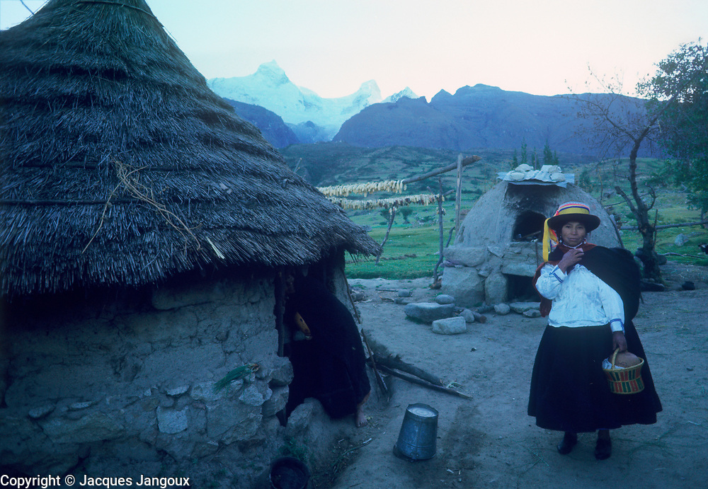 Peru, Cordillera de los Andes, Andes mountain range, Cordillera Blanca. Quecha Indian woman near house at early morning in mountains.