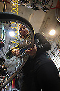 New York, N.Y. October 31, 2013. At the bike shop where she works on the Lower East Side, Liz Jose fixes the tire on a bike that's being repaired. 10/31/2013. Photo by Erin Brodwin/NYCity Photo Wire