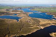 Nederland, Noord-Holland, Naarden, 16-04-2008; Naardermeer: oudste en een van de bekenste natuurreservaten van Nederland, bezit van de Vereniging voor Natuurmonumenten (grondlegger Jac. P. Thijsse); rechts aan de horizon windmolens bij Muidezand (Flevoland) en aan het water Muiderberg; rechts op driekwart autosnelweg A1, ongeveer in het midden komt de A6 uit Almere op knooppunt Muiderberg er bij; momenteel wordt het gebied uitsluitend doorsneden door de spoorlijn, er zijn echter plannen om een nieuwe weg aan te leggen tussen het nabij gelegen Almere en Amstelveen / Schiphol, in verband met de fileproblematiek rond de hoofdstad; Rijkswaterstaat overweegt echter de Gaasperdammerweg te verbreden ivm die files en zo het Naardermeer te sparen;..luchtfoto (toeslag); aerial photo (additional fee required); .foto Siebe Swart / photo Siebe Swart