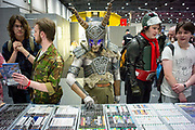UNITED KINGDOM, London: 25 May 2018  A cosplay fan takes a look at video games at one of the many stalls inside of the MCM London Comic-Con this afternoon. The three day comic convention, which is held at London's ExCeL, will see thousands of visitors many of them in cosplay, dressed as their favourite super hero, villain or comic book character. Rick Findler  / Story Picture Agency