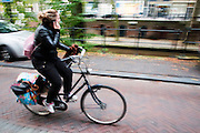 In Utrecht fietst een meisje al bellend over de Oudegracht.<br /> <br /> In Utrecht a girl cycles at the Oudegracht while phoning.