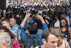 London, August 29th 2016. A man takes a picture with his smart phone of the thousands of people on Portobello Road during day two of Europe's biggest street party, the Notting Hill Carnival.