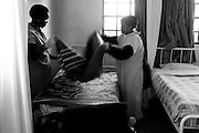 Nurses making a bed at the Footprints Hospice 14 August 2009 Orlando East Soweto, South Africa. Footprints Hospice was opened by the Soweto Retired Professional Society (SRPS)  in August 4 2004 by retired nurses from Chris Hani Baragwanath Hospital. .