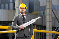 Portrait of confident young architect holding blueprints outside industry